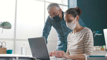 Professional business people working together in the office, they are wearing protective face masks, coronavirus covid-19 prevention concept