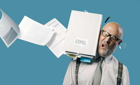 Flying paperwork hitting and hurting a businessman's head, unexpected payments and crisis concept Stock Photo