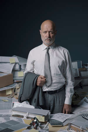 Stressed senior businessman overloaded with paperwork, he is standing, feeling hopeless and exhausted Imagens