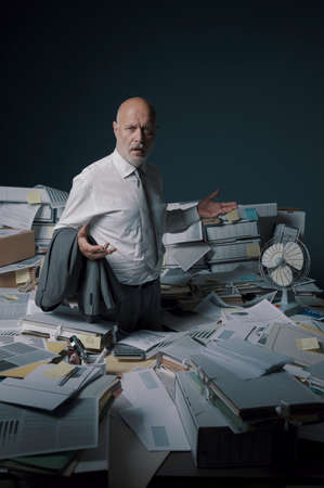 Disappointed stressed businessman standing in his office surrounded by lots of paperwork