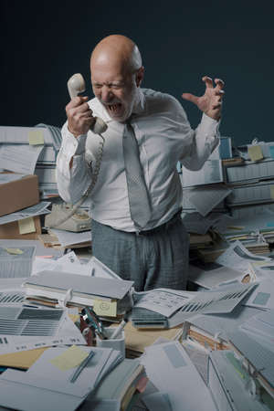 Stressed business executive overwhelmed by work, he is surrounded with paperwork and shouting at the telephone receiver