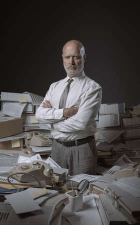 Confident serious businessman posing in his messy office with arms crossed, he is overloaded with paperwork