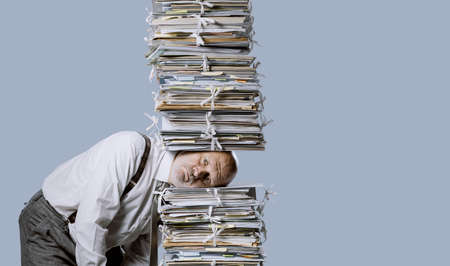 Stressed businessman under a pile of paperwork, he is overwhelmed by work Imagens