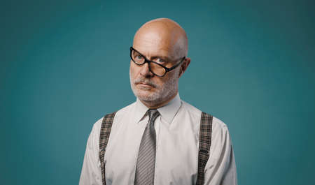 Frustrated serious businessman with crooked glasses, he is staring at camera