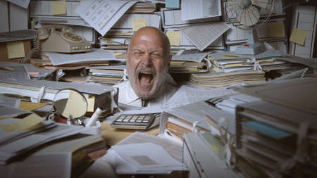 Stressed businessman buried under a lot of paperwork, he is angry and screaming
