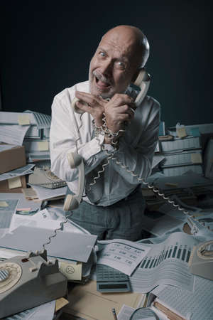 Stressed businessman working in a messy office, he is holding many telephone receivers and he is surrounded by lots of paperwork