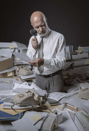 Inefficient businessman overloaded with paperwork, he is checking a document with a loupe
