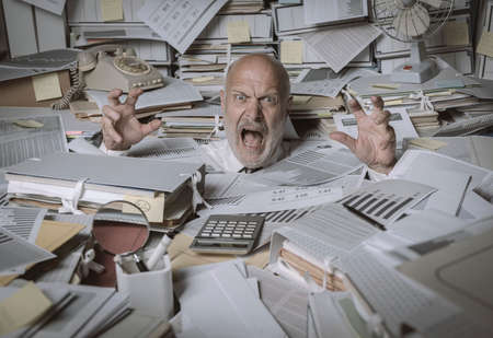Screaming businessman drowning under a lot of paperwork in the office, he is overwhelmed by work and going insane Imagens