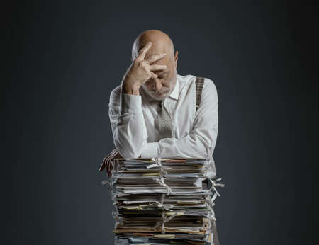 Pensive worried businessman leaning on a pile of paperwork, bureaucracy and administration concept