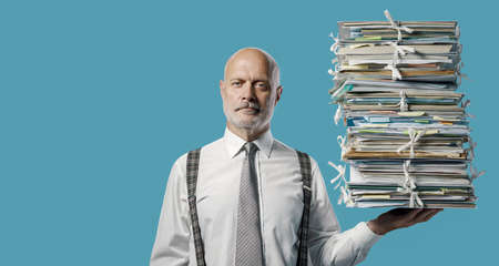 Confident businessman holding a pile of paperwork effortlessly with one hand, easy business administraton concept Imagens