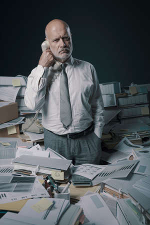 Confused stressed office worker answering phone calls, he is surrounded by lots of paperwork