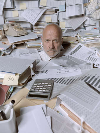 Disappointed stressed businessman overwhelmed by paperwork, he is stressed and looking at camera