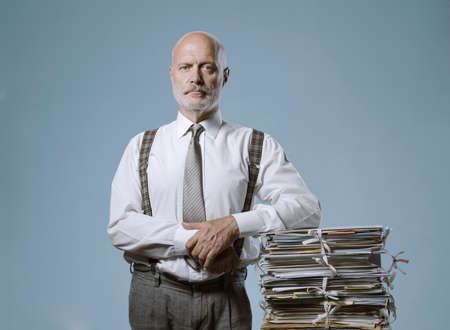 Confident businessman posing with a pile of paperwork, leadership and business concept