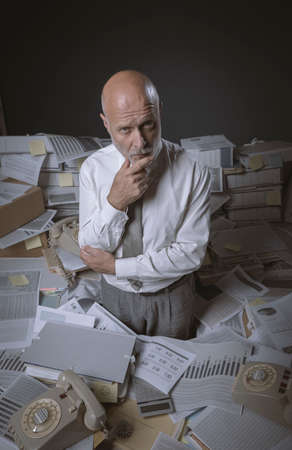 Pensive stressed businessman surrounded by paperwork in the office, he is thinking with hand on chin Imagens