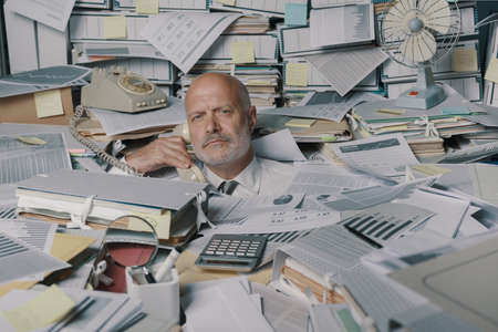 Stressed businessman overwhelmed by work, he is drowning under a lot of paperwork and answering phone calls