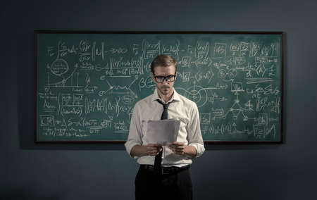 Confident young math professor standing in front of the chalkboard and explaining formulas, mathematics and academic research concept