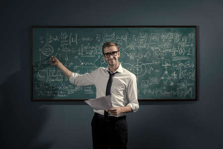 Confident young math professor standing in front of the chalkboard and explaining formulas, he is pointing and smiling