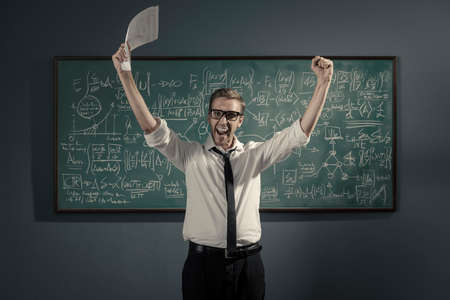 Cheerful successful mathematician standing in front of a chalkboard with math formulas, he solved the problem and he is celebrating