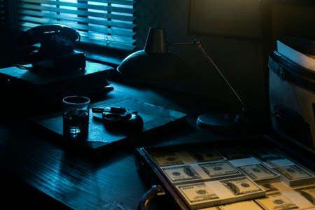 Vintage film noir style desktop with revolver, drink and open briefcase full of cash money: mafia, crime and thriller concept