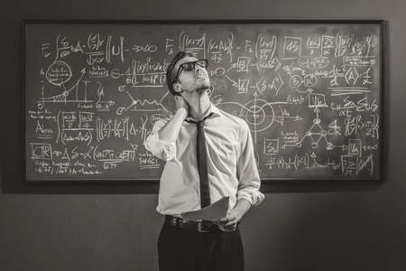 Math student standing in front of the chalkboard and feeling confused, he is not able to solve the problem