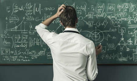 Young mathematician solving problems and writing formulas on the chalkboard, back view