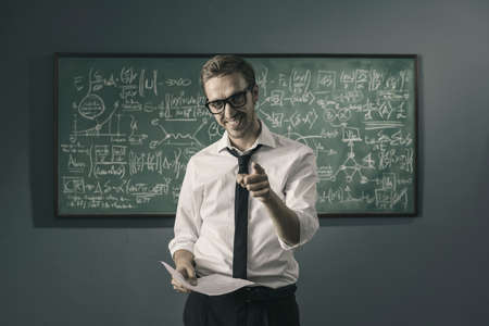 Confident smiling professor standing in front of a chalkboard with math formulas and pointing at camera
