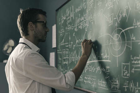 Young smart mathematician drawing math formulas on the chalkboard and thinking: he is solving problems and discovering new theories