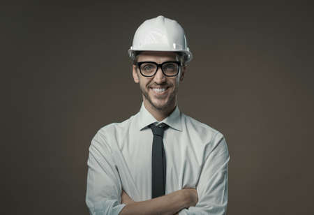 Confident architect smiling and wearing a safety helmet, construction industry and engineering concept Archivio Fotografico