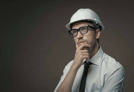 Construction engineer thinking with hand on chin: problem solving and planning concept