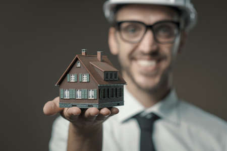 Smiling architect holding a model house, real estate and construction industry concept