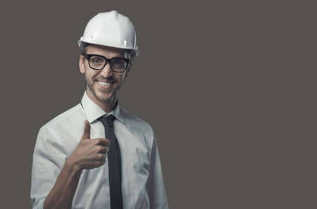 Smiling confident architect wearing a safety helmet and giving a thumbs up Archivio Fotografico