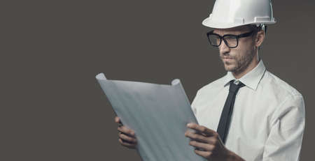 Professional architect wearing a hardhat and checking a house project, real estate and construction industry concept