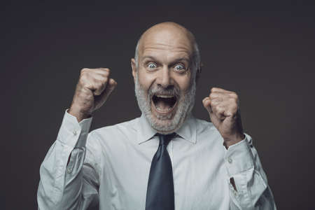 Cheerful smiling businessman celebrating with raised fists, successful business concept Archivio Fotografico