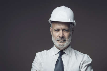 Smiling businessman wearing a safety helmet, engineering and safe business concept