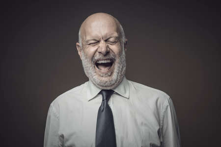 Cheerful middle-aged corporate businessman laughing out loud