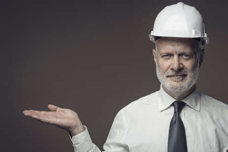 Smiling middle-aged businessman and engineer wearing a safety helmet and presenting something to the camera