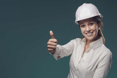 Smiling woman wearing a safety helmet and giving a thumbs up, safety at work concept