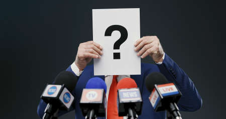 Politician hiding his face with a sign with question mark during a press interview, he is hiding his identity