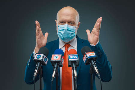 Politician wearing a surgical mask and talking to the media, election campaign concept