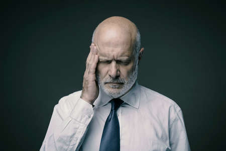Exhausted stressed middle-aged businessman having a bad headache, he is tired and overworked Stock Photo