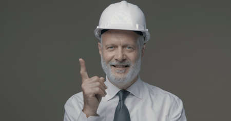 Cheerful businessman and engineer wearing a safety helmet and pointing upwards