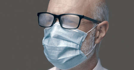 Senior man with glasses fogging up while wearing a protective face mask