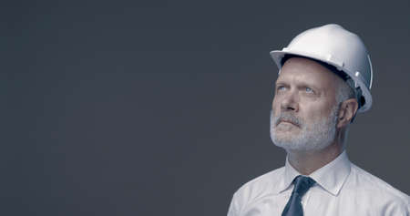 Confident businessman and engineer posing with a safety helmet, he is looking away and thinking