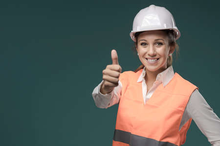 Smiling young woman wearing a safety vest and safety helmet, safety at work and protective workwear concept