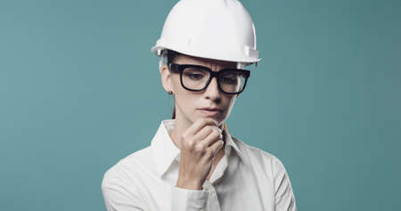 Pensive young businesswoman wearing a safety helmet and thinking with hand on chin