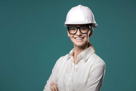 Smiling cheerful businesswoman wearing a safety helmet and looking at camera Archivio Fotografico