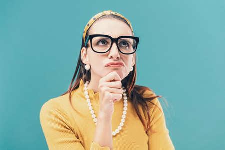 Confused clueless woman thinking with hand on chin, she is taking a decision Standard-Bild