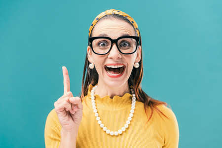 Cheerful retro style woman smiling and pointing up, ideas and advertising concept