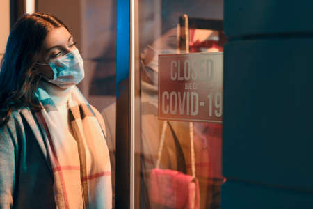 Store closed due to coronavirus covid-19 outbreak, a woman with surgical mask is reading the sign