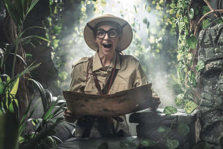 Cheerful woman exploring a tropical jungle with a map, she finds some ancient ruins
